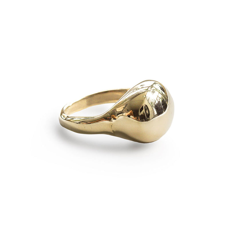 brass globe ring on white surface by delia langan jewelry