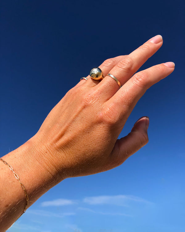 woman hand wearing globe ring on ring finger and thin gold stacking rings on middle and pinky fingers against blue sky