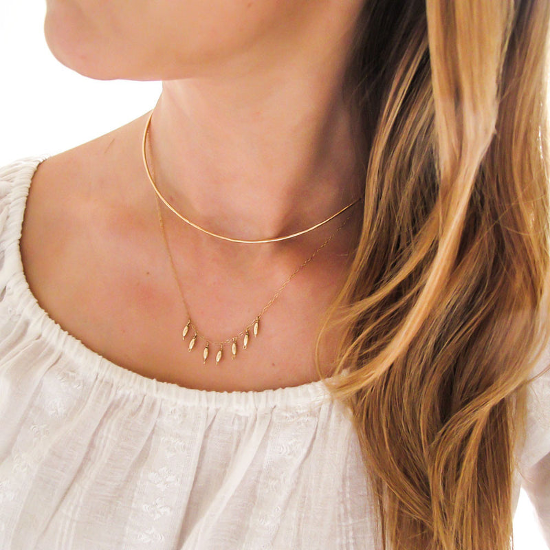 blond woman on a white blouse wearing a 14k gold filled gold grain necklace