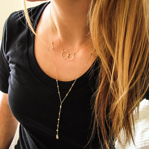 blond woman on a black tshirt wearing a 14k gold filled prism y necklace