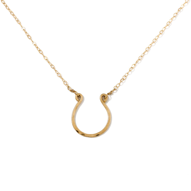 14k gold filled good luck horseshoe necklace on a white surface