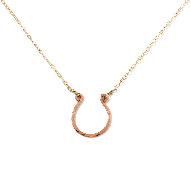 rose gold filled good luck horseshoe necklace on a white surface