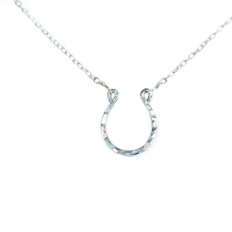 shining horseshoe closeup of a sterling silver good luck horseshoe necklace under a bright light