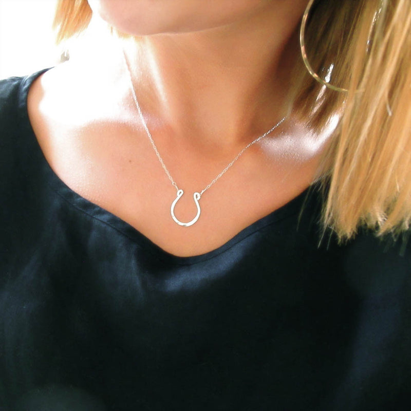 blond woman on a black shirt wearing a sterling silver good luck horseshoe necklace