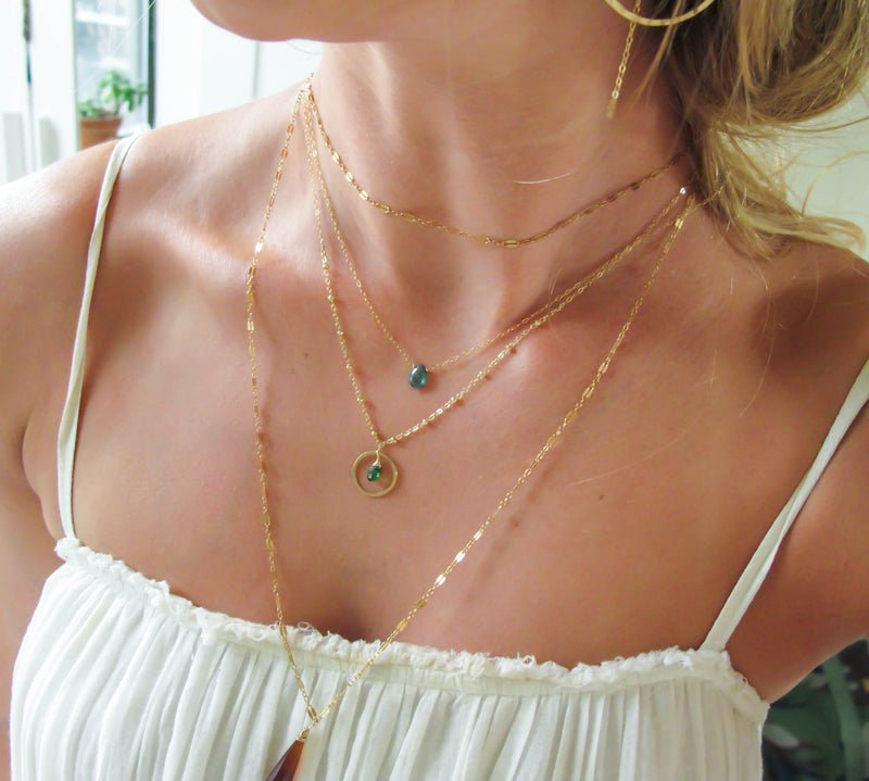 blond woman on a white top wearing a 14k gold filled green tourmaline unity gemstone necklace