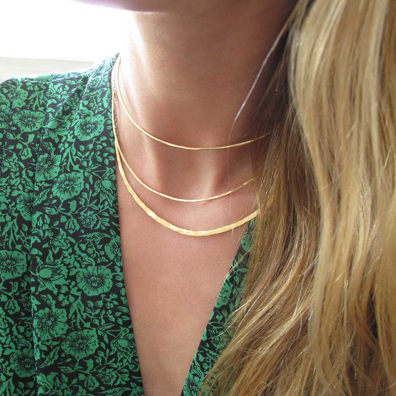 blond woman on a green jumpsuit wearing a 14k gold fill xl scenic route necklace and two 14k gold fill halo collars