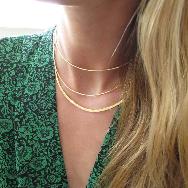 neck closeup of a blond woman on a green jumpsuit wearing a 14k gold filled crescent collar necklace