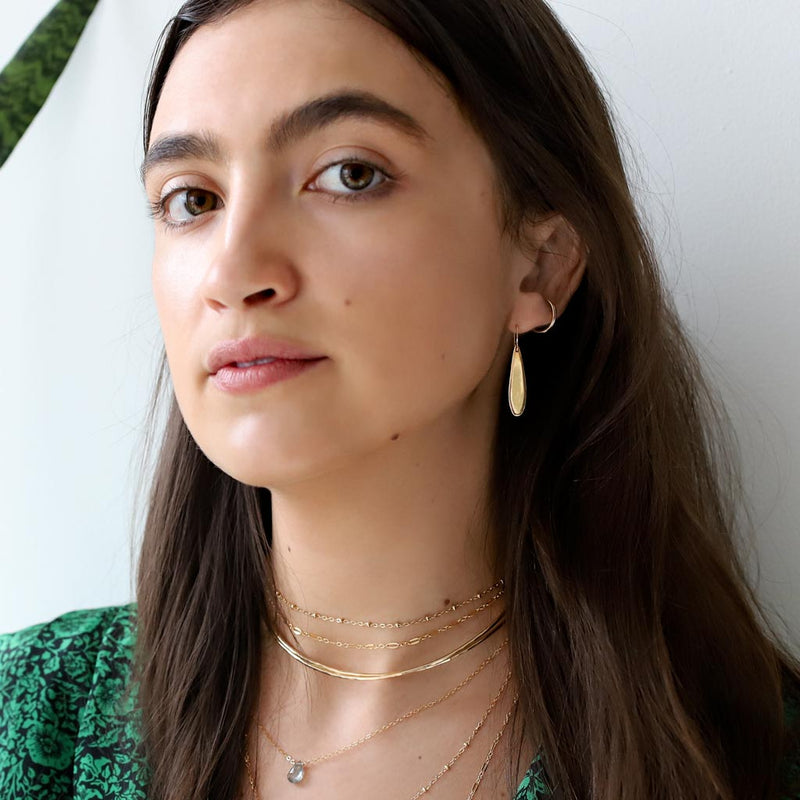 woman with small gold teardrop earrings and layered gold necklaces