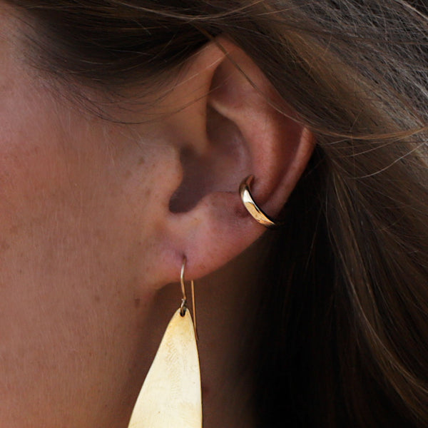 Woman wearing a Gold Hugh Hoop and drop-shaped gold earring closeup