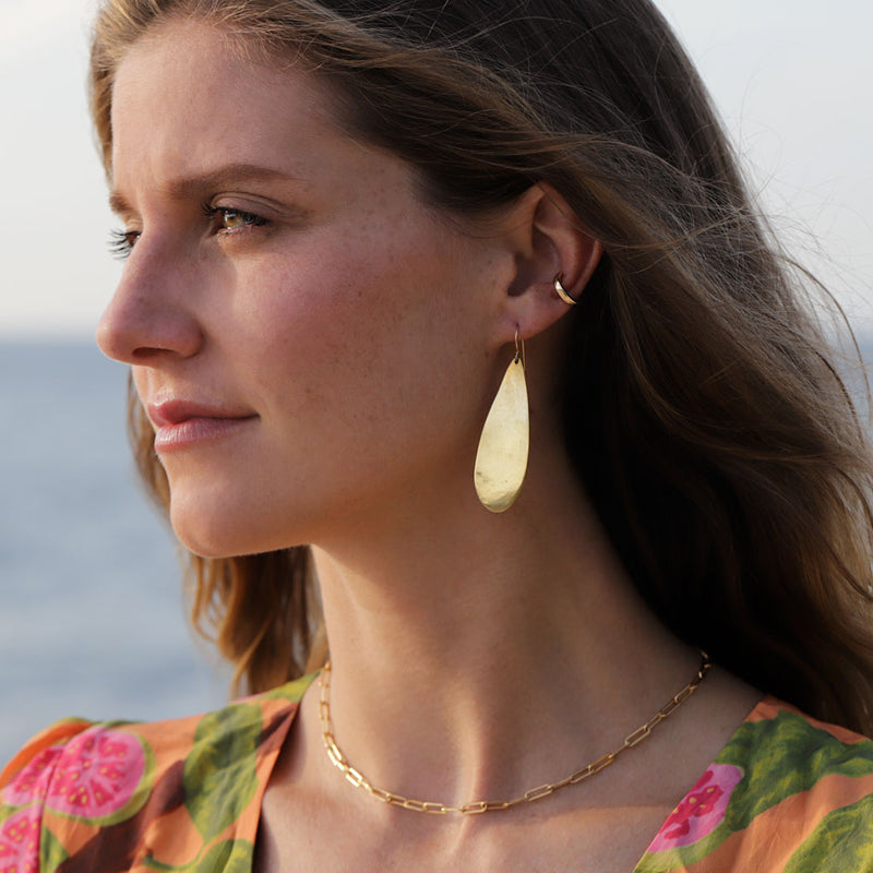 Woman wearing a hug hoop, Big drop shaped gold earring, and gold link necklace at the beach