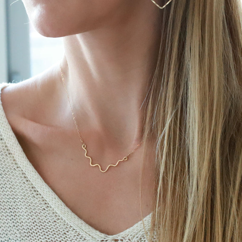 blond woman on a white v neck wearing a 14k gold filled im hammered necklace