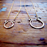 tiny gold horseshoe pendants by delia langan jewelry