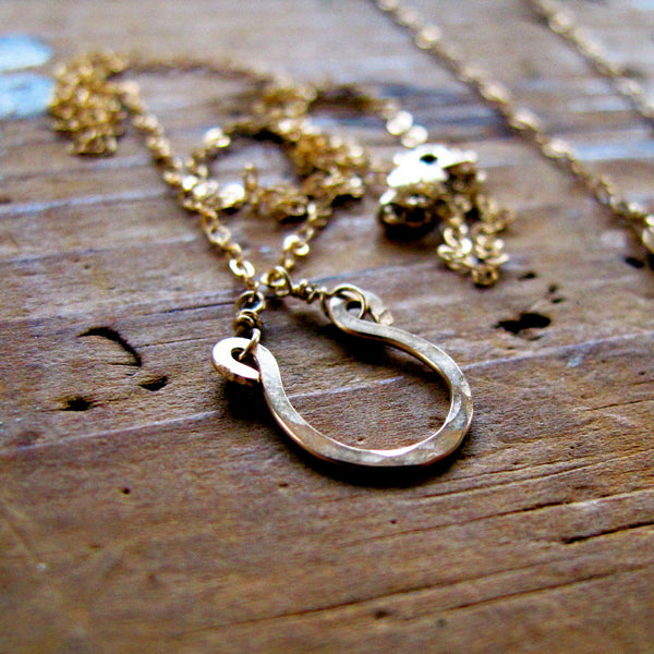 tiny gold horseshoe pendant by delia langan jewelry