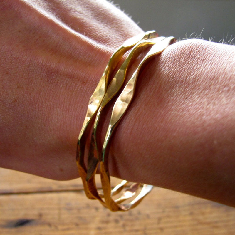 wrist closeup wearing 3 brass im hammered wavy bangles partially under light reflecting light