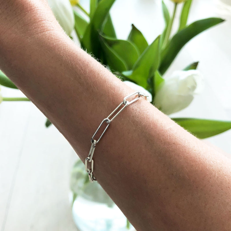 woman wrist wearing a sterling silver large link chain bracelet on a white tulips background