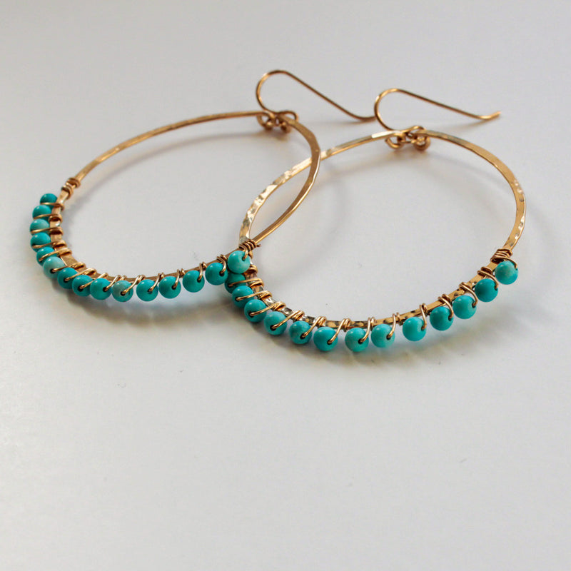 side view of wire wrapped turquoise 14k gold filled hammered hoop earrings handmade by delia langan