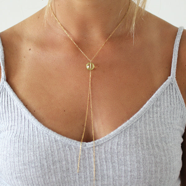 blond woman on a white top wearing a 14k gold filled lemon quartz y gemstone necklace