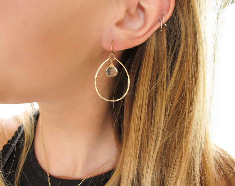 blond woman ear closeup wearing 14k gold filled green amethyst teardrop gemstone hoops