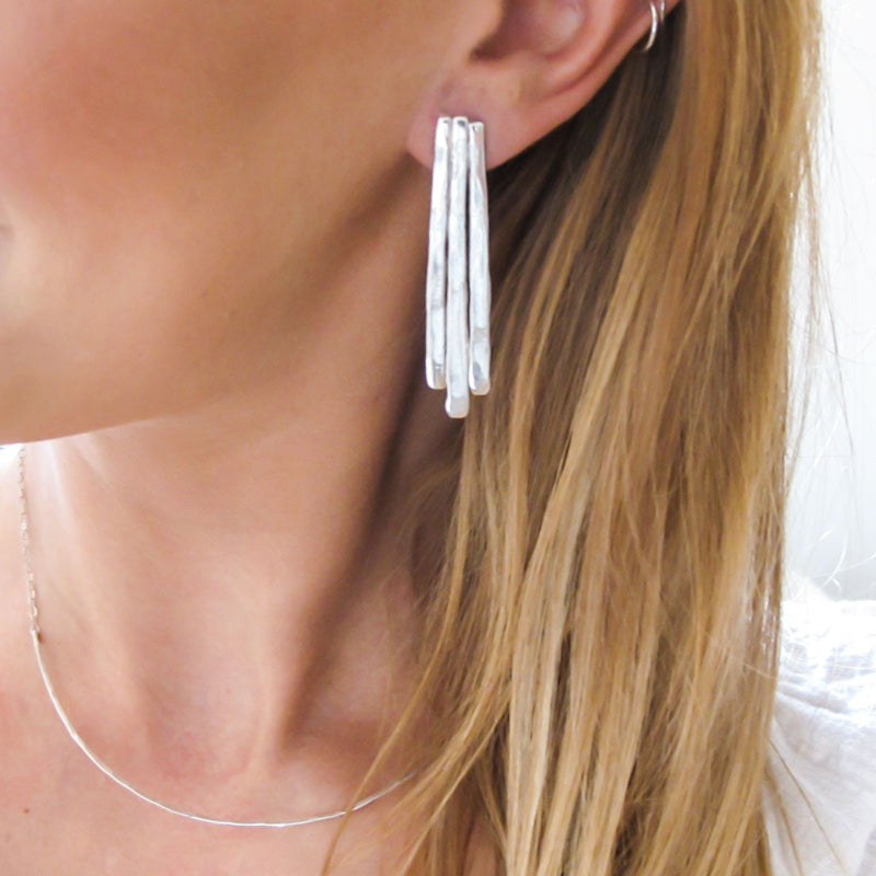 blond woman ear closeup wearing sterling silver long fringe post earrings