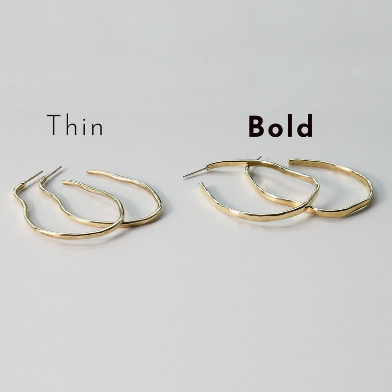 brass with sterling posts maeve thin hoop earrings next to brass with sterling posts maeve bold hoop earrings on white surface