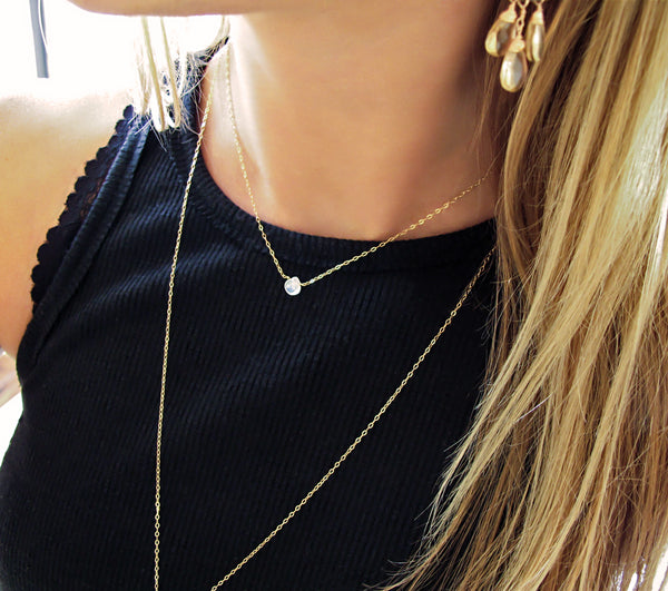blond woman on a black tank wearing a 14k gold filled moonstone short gemstone necklace