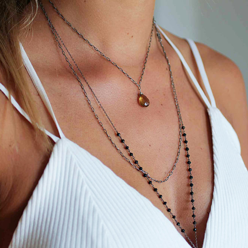blond woman cleavage wearing an oxidized sterling silver long y black spinel gemstone necklace