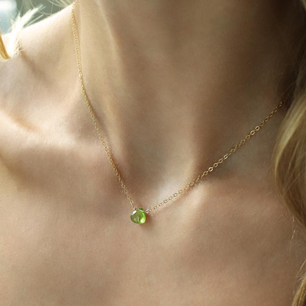 woman neck close up wearing a 14k gold filled peridot short gemstone necklace