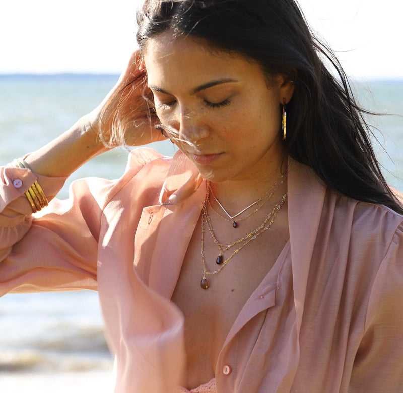 brunette at beach on a pink shirt against wind looking down wearing a 14k gold fill garnet short gemstone necklace
