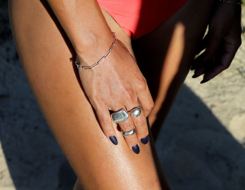 Woman wearing big silver rings, link bracelet and a bikini at the beach