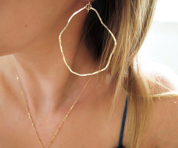 closeup of gold wavy irregular hoop earrings hand hammered and handmade by delia langan jewelry