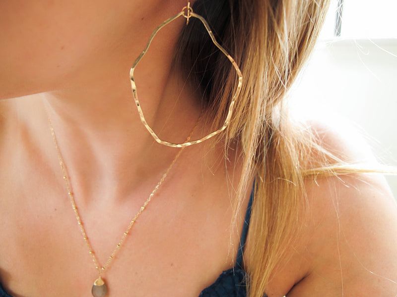 blond woman ear closeup wearing 14k gold filled potatohead hoop earrings