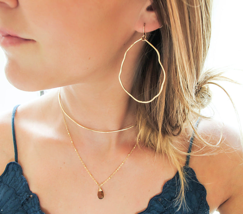 blond woman on a dark green top wearing 14k gold filled potatohead hoop earrings