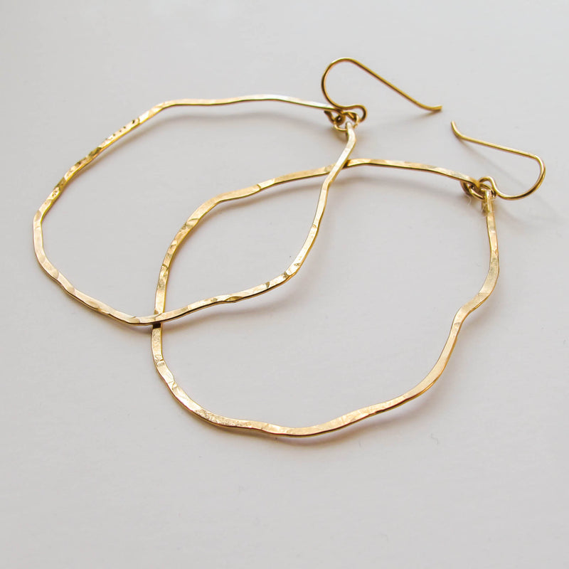 side view of gold wavy irregular hoop earrings hand hammered and handmade by delia langan jewelry
