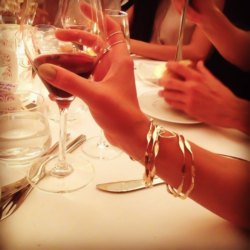 woman hand holding a wine glass wearing 5 brass im hammered wavy bangles at fancy dinner with friends