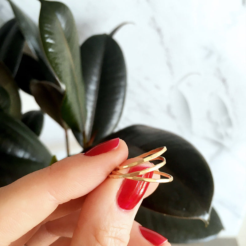 red nails woman hand holding 3 thin 14k gold filled stacking rings on a green leaves background