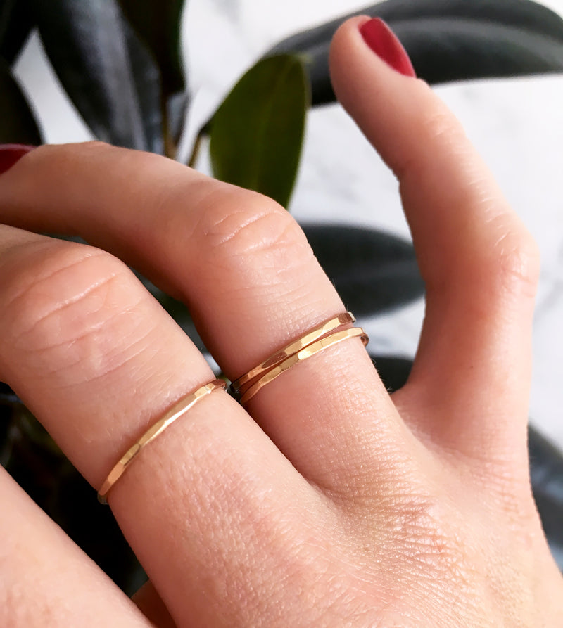 three thin gold stacking rings on hand by delia langan jewelry
