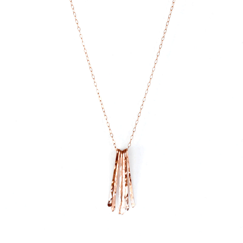 rose gold filled different strokes fringe pendant necklace on a white surface