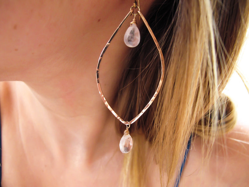 blond woman on a blue top ear closeup wearing rose quartz rose gold leaf gemstone earrings partially reflecting light