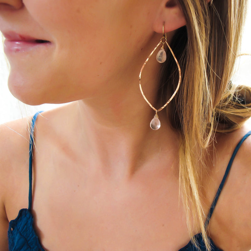 blond woman on a blue top wearing rose quartz rose gold leaf gemstone earrings