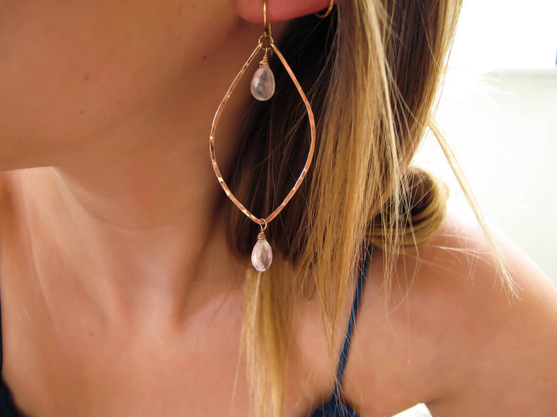 blond woman on a blue top ear closeup wearing rose quartz rose gold leaf gemstone earrings