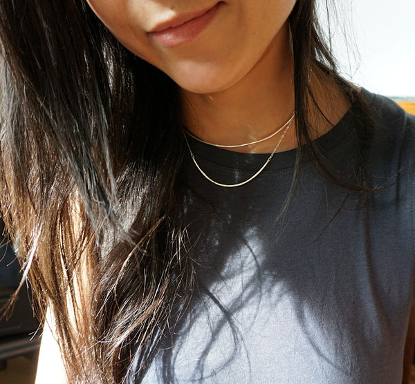 brunette on a navy blue tshirt wearing a sterling silver scenic route necklace partially under sunlight