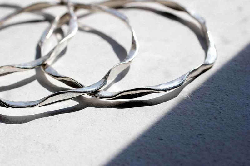 closeup of three sterling silver I'm hammered wavy bangles on a grey surface under sunlight reflecting light