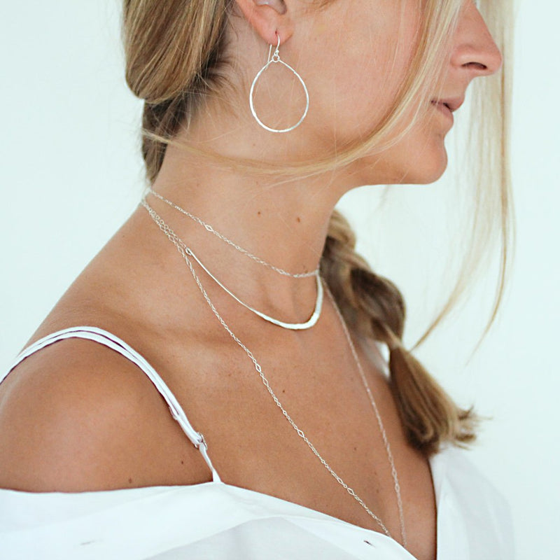 girl with delicate silver layering necklaces and silver oval hoops