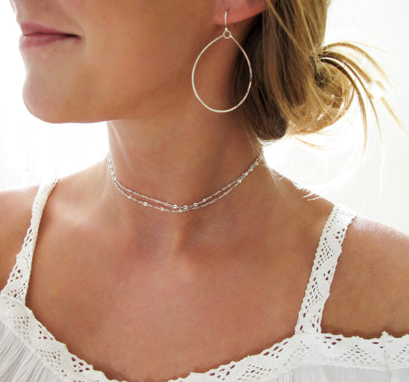 blond woman on a white top wearing sterling silver hoops for nuns hoop earrings