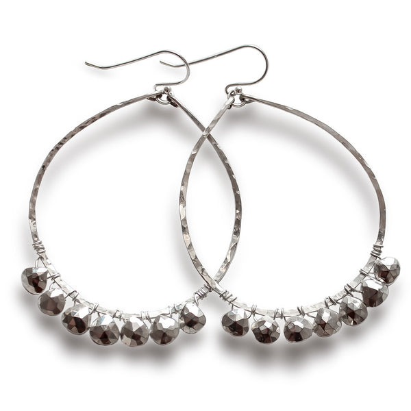 sterling silver silver metallic party girl hoops on a white surface partially under a bright light