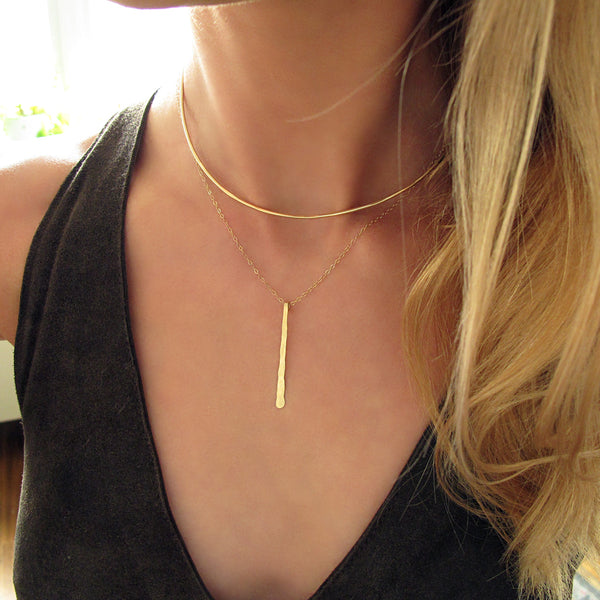 blond woman on a black top wearing a 14k gold filled single stroke necklace