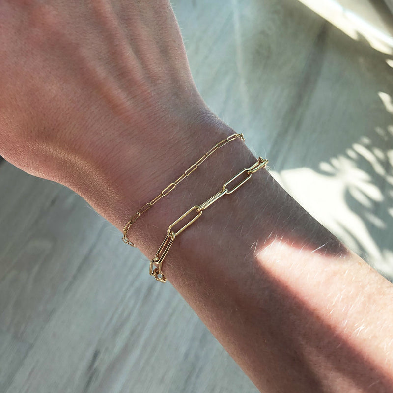 woman wrist wearing 14k gold filled small link and large link chain bracelets against wood floor
