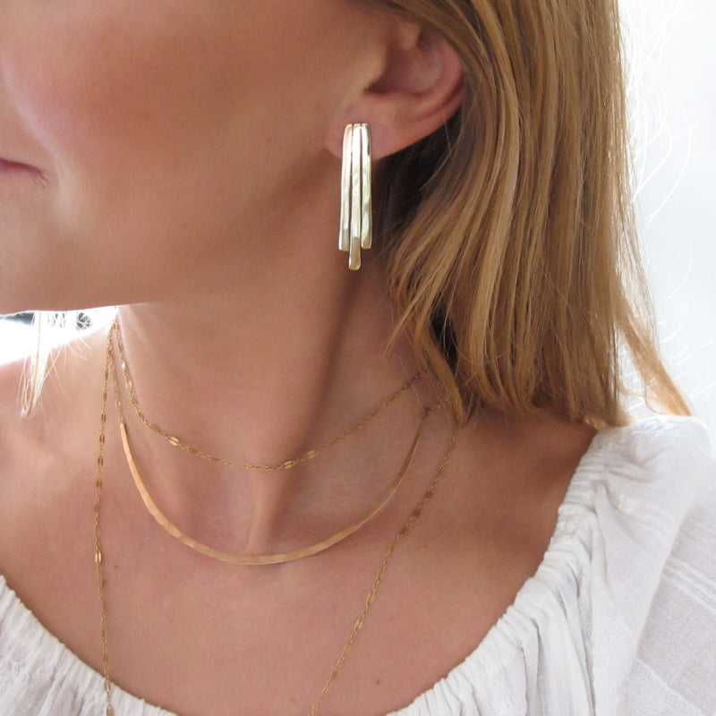 blond woman neck closeup wearing gold brass small fringe post earrings