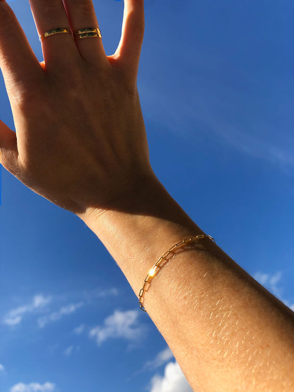 woman hand wearing thin gold stacking rings on middle and ring fingers and a 14k gold filled small link chain bracelet