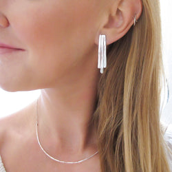 blond woman neck closeup wearing sterling silver small fringe post earrings